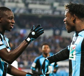 Michy Batshuayi of Marseille celebrates with teammate Benjamin Mendy after scoring the first goal during the French Cup game between US Granville V Olympique de Marseille at Stade Michel D'Ornano on March 3, 2016 in Caen, France.